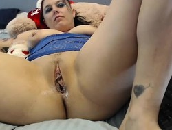 Plump brunette lies in bed and strokes her moist pussy on